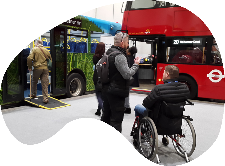 A wheelchair user and a friend signing with a red double decker bus in the background